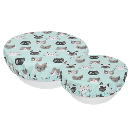 A pastel blue bowl cover with gray, black, and/or white cat heads all over it.