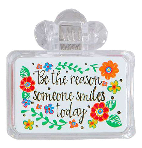 """Be the reason someone smiles today"" is painted in black on a white background. A bright and colorful floral design borders the quote."