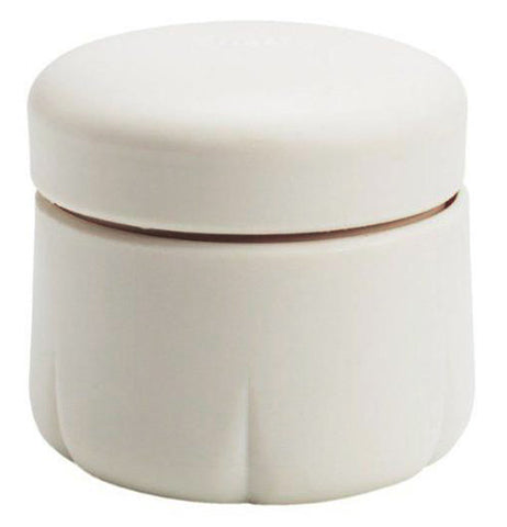 A white garlic peeler canister with top on.