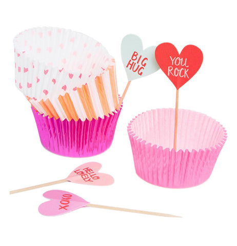 "These pink, orange, and white cupcake holders each hold small heart signs, one blue with the words, ""Big Hug"" in red lettering, another red with the words, ""You Rock"" in white lettering. Two pink heart signs are shown with words such as, ""Hello Lovely"" and ""XOXO"" in red lettering."