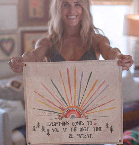 "A lady holds the ""Be Patient"" Wall Hanging Art."