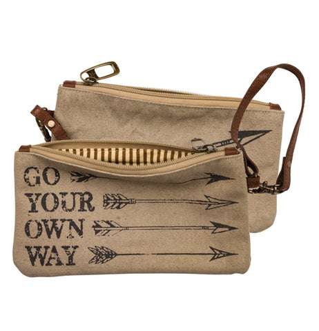 "Tan, brown, and black canvas wallet wristlet that says ""Go Your Own Way"" with arrows design exterior and striped interior with zipper closure and strap handle on a white background."