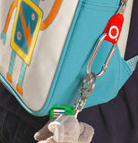 The blue and white robot backpack is shown in this image. From the side hangs a small stuffed animal hanging from a clip.