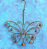 "This Filigree Windchime ""Butterfly"" hangs against the blue and purple background."