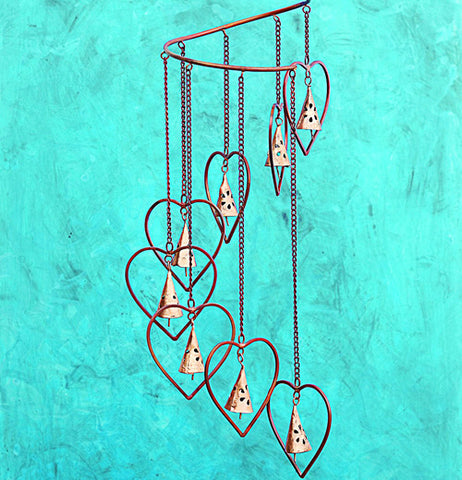 "This hanging Spiral Marble ""Hearts and Bells"" hangs on a turquoise background."