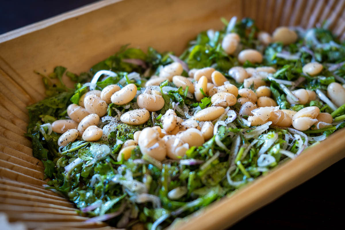 Cooked Rancho Gordo Alubia Blanca beans over greens, herbs, and onions