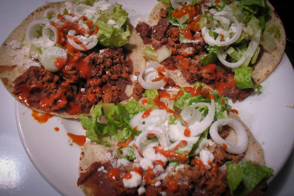 Three tacos with refried Pinto beans topped with onion, lettuce, and feta - Rancho Gordo, Heirloom beans