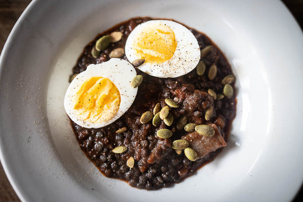 Cooked black caviar lentils topped with half cut boiled egg and seeds-Rancho Gordo