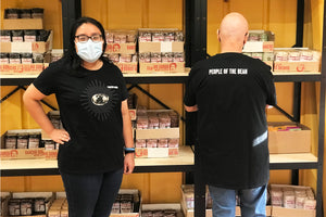 Woman with a Rancho Gordo tee shirt and mask next to a bald man, showing the back of the shirt.