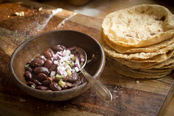 Cooked Ayocote Morado, topped with diced onion with a side of homemade tortillas-Rancho Gordo, Heirloom beans.