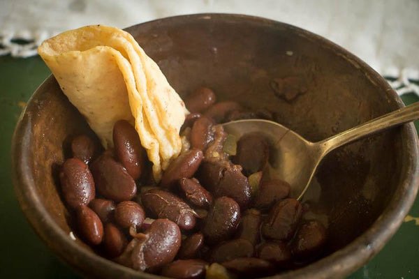 Bowl of cooked Ayocote Morado beans with a rolled up tortilla-Rancho Gordo, Heirloom beans.