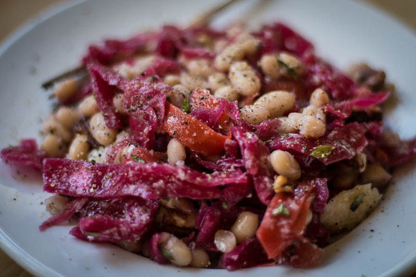 Cooked Alubia Blanca mixed with sautéed red cabbage and tomatoes, sprinkled with black pepper-Rancho Gordo, Heirloom beans.