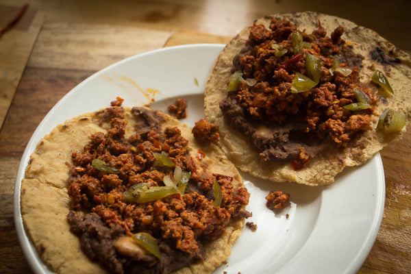 Two tacos with refried beans and chorizo topped with cut jalapeños - Rancho Gordo, Heirloom beans