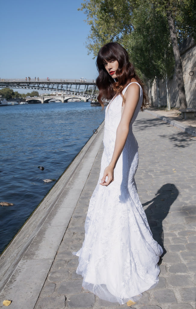 model standing next to the River Seine wearing a wedding dress while twirling on a sunny day.