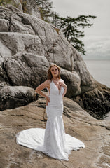 Pacific NorthWest bride wearing comfortable fitted lace wedding dress while standing on rock.