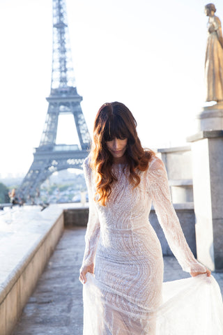 Bride in Paris wearing beaded backless wedding dress, while looking down.