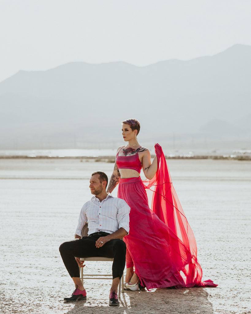 Final wedding dress photos of bride in pink wedding dress and groom in the desert.
