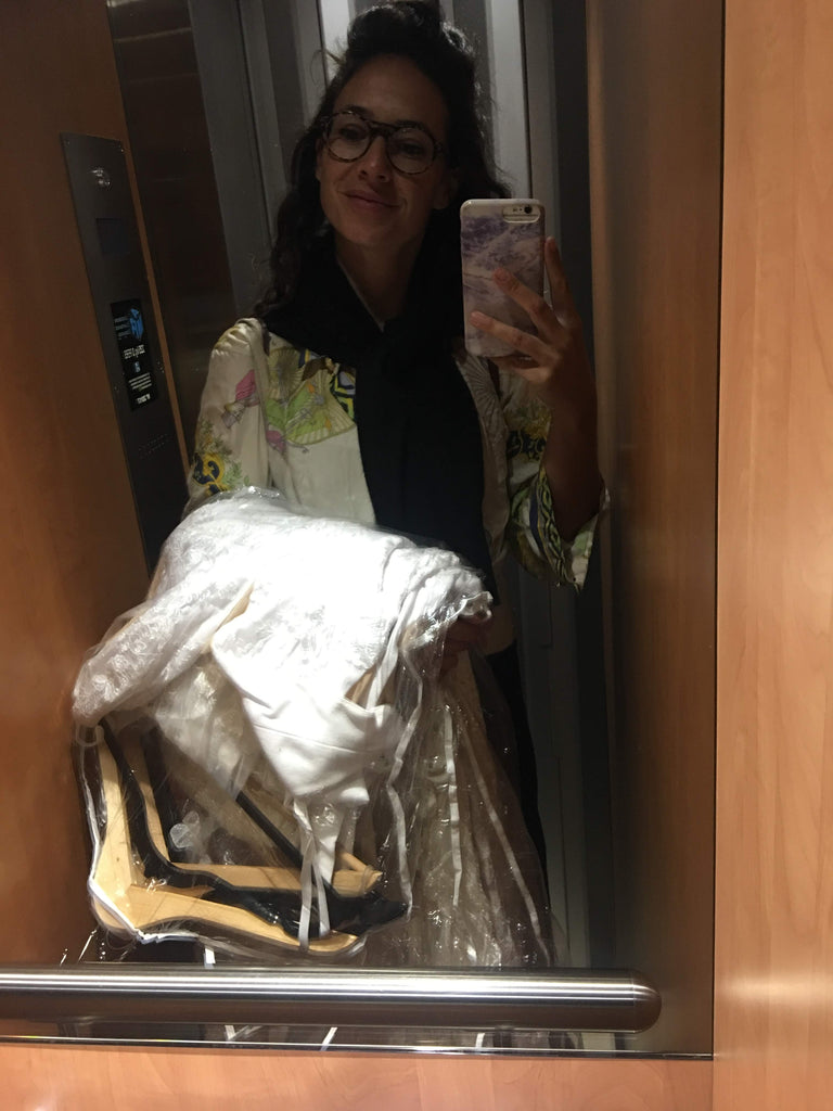 Hrissa, designer of Elika In Love, holding wedding dresses in a small elevator in Paris.