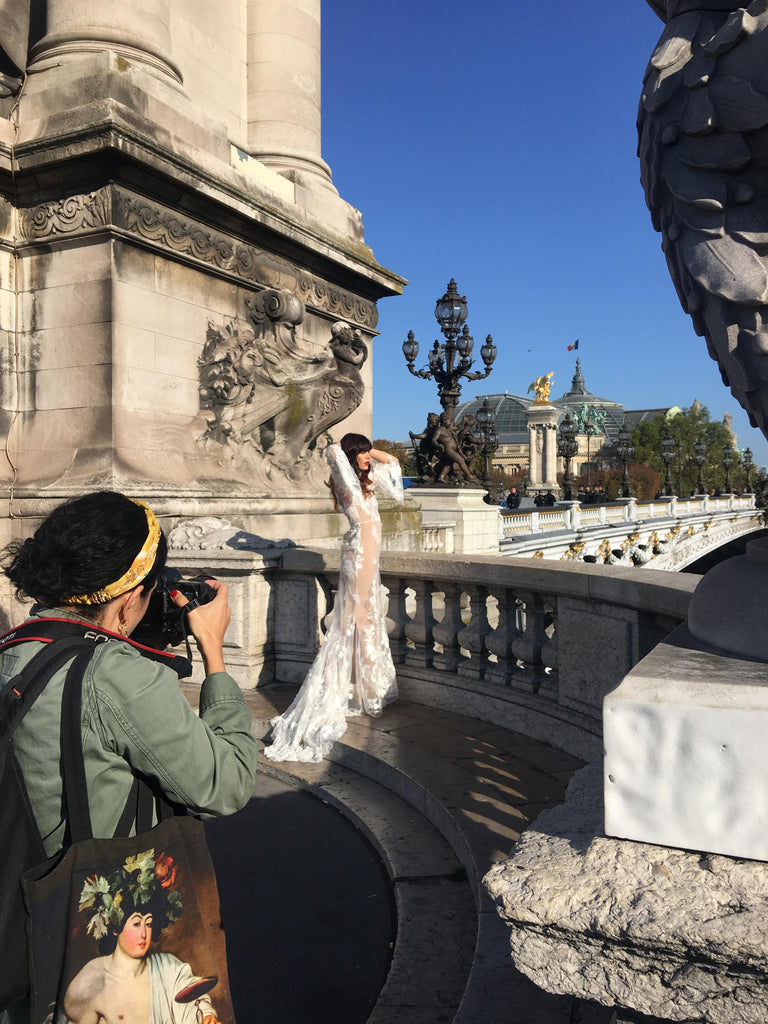 Photographer taking a photo of model posing in wedding dress on a bridge in paris.