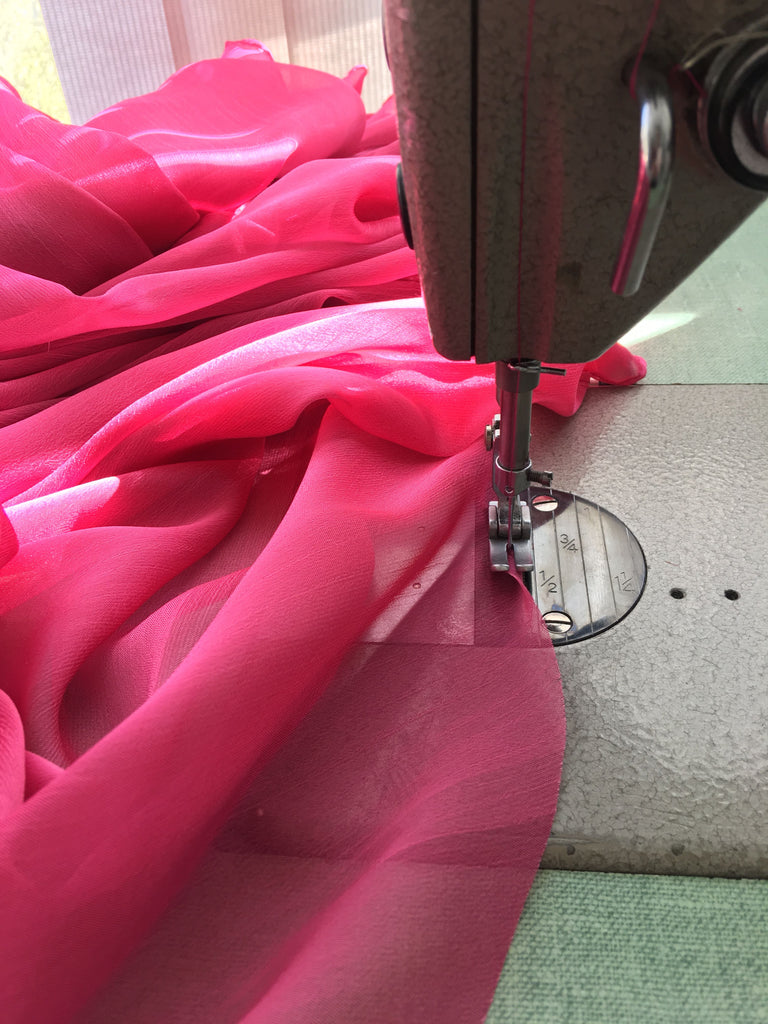 Sewing machine sewing chiffon of custom wedding dress in pink for Elika In Love's Vancouver bride.