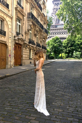 Bride standing in front of Eiffel Tower in backless lace wedding dress.