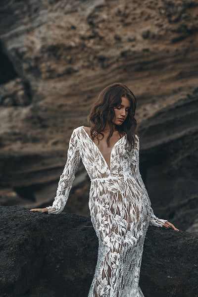 Bride wearing a long sleeve wedding dress on a black rock in Bali.