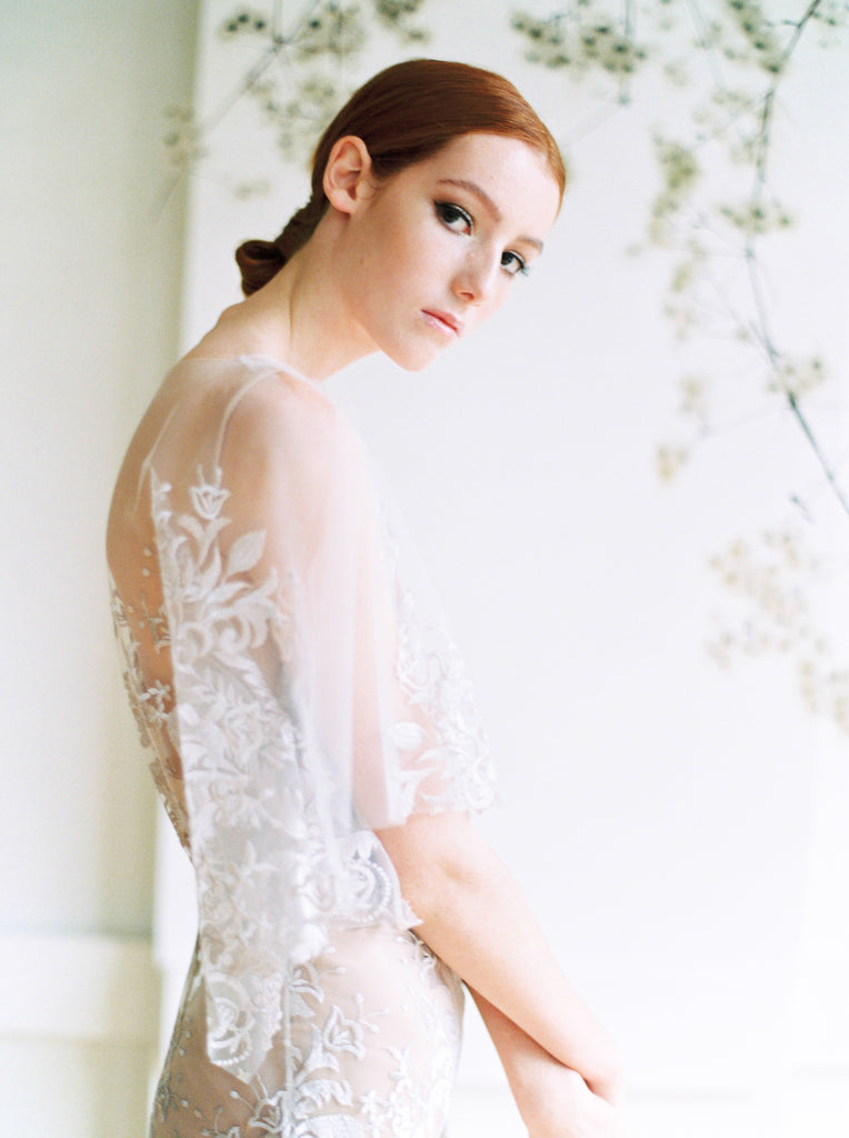 Romantic boho wedding dress with bride in side view, head down, looking at the camera.