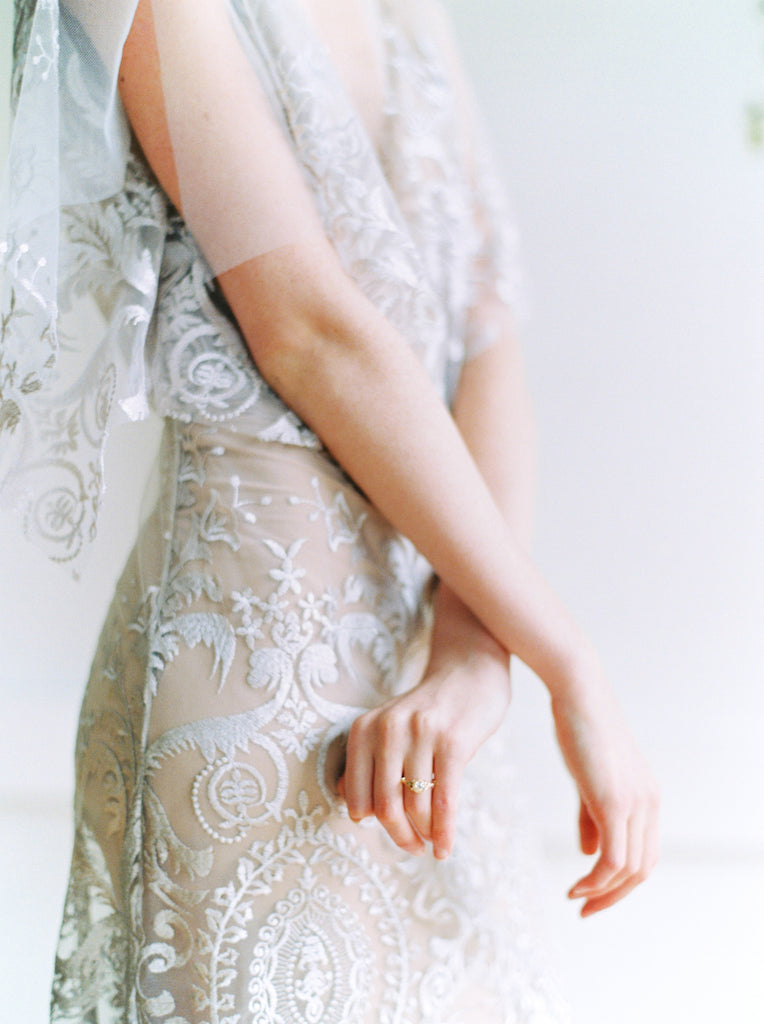 Close-up of woman's torso wearing boho lace wedding dress by Vancouver designer Elika In Love.