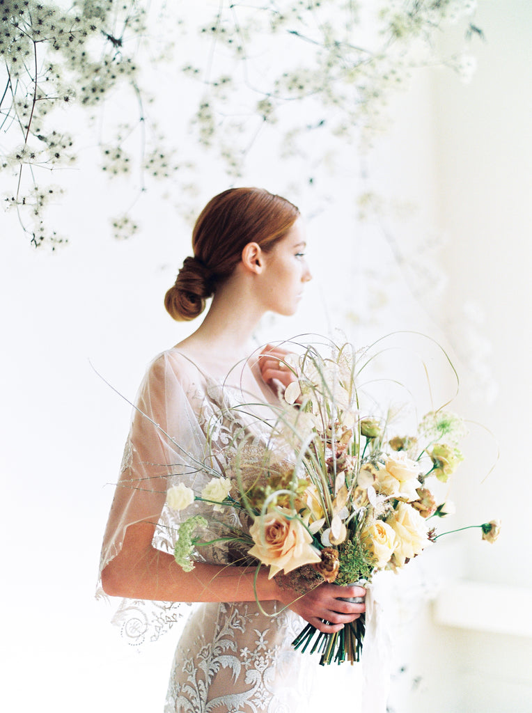 VANCOUVER BRIDAL SHOPs helping brides style romantic boho wedding dresses by showing a bride in the Elle gown, full length profile shot holding bridal bouquet..