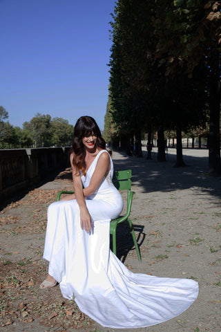 Bride wearing white wedding dress while sitting in chair in park.