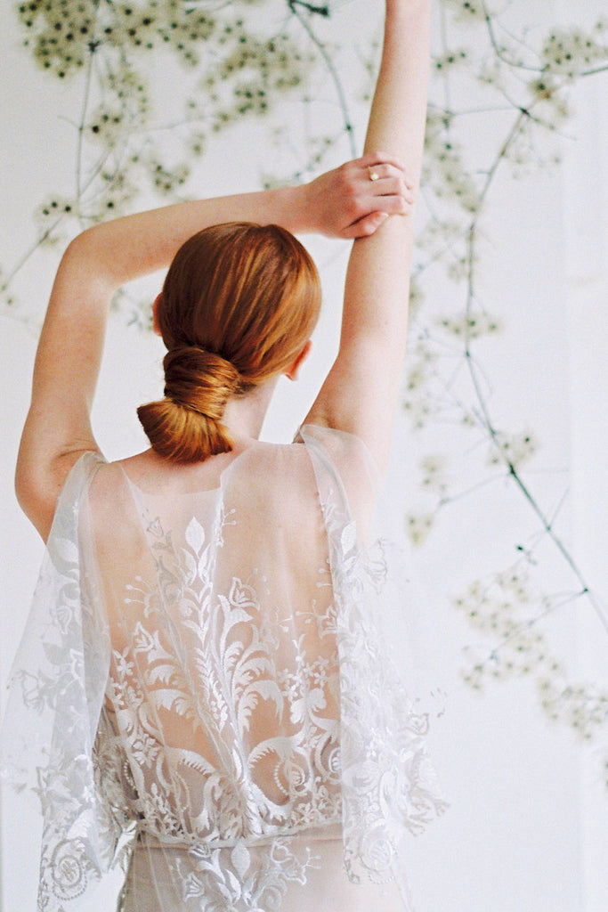 boho inspired wedding dresses with bride facing away from the camera, arms up, in a wedding dress.