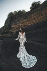 Bride leaning against black rock with long sleeve lace wedding dress fanned in front of her.