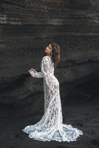 Bride with hands on rock facing away, wearing long sleeve white lace dress.