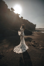 Load image into Gallery viewer, Bride on beach with hands in air showing boho sleeves and long train of wedding dress.