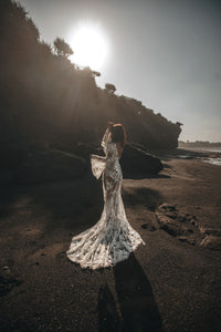 Bride on beach with hands in air showing boho sleeves and long train of wedding dress.