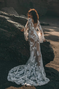 Bohemian bride in hippie wedding dress leaning against rock on beach.