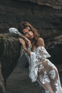 Sexy pose of model showing shoulder leaning against rock in lace wedding dress.
