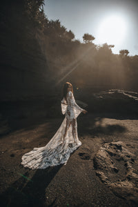 Full length side shot of model on sunny beach with long train of lace overlay wedding dress.