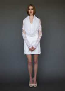 Model standing facing us, in long sleeve lace bridal jacket with draped neckline.