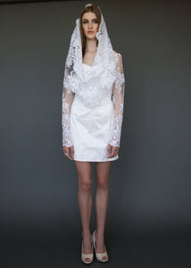 Model standing, in short wedding dress and lace cropped jacket.