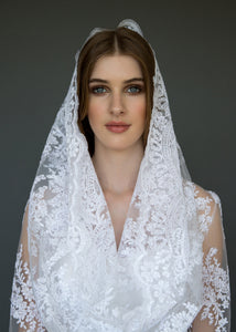 Model close-up in bridal veil and lace jacket.