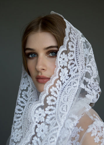 Close up of side of face, model wearing bridal veil and bolero.