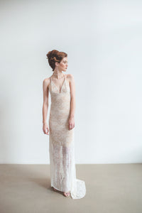 A different wedding dress made from lace with an open back and long train.