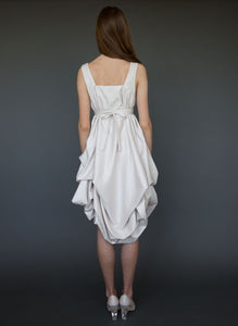 Model full length facing away, wearing greek style short wedding dress.