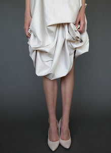 Close up of skirt of hand draped silk short wedding dress.