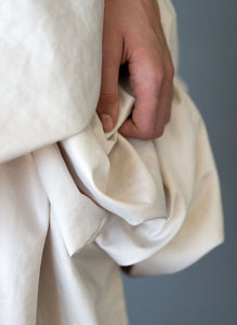 Fabric detail shot of hand, short draped wedding dress available in Vancouver shop.