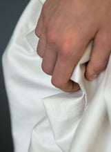Load image into Gallery viewer, Detail of fabric and hand of silk draped Grecian wedding dress.