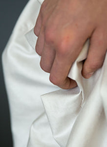 Detail of fabric and hand of silk draped Grecian wedding dress.