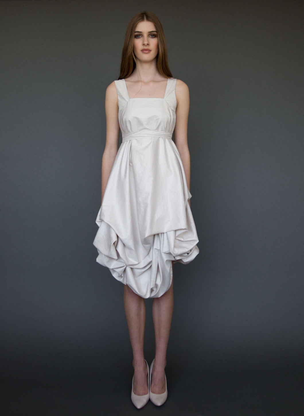 Model posing full length wearing short, belted, A-line wedding dress with straps.
