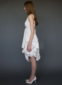 Model, full length, side view, wearing sleeveless below the knee maternity short wedding dress.